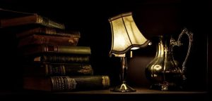 ancient-lamp-with-silver-jug-and-books-on-table
