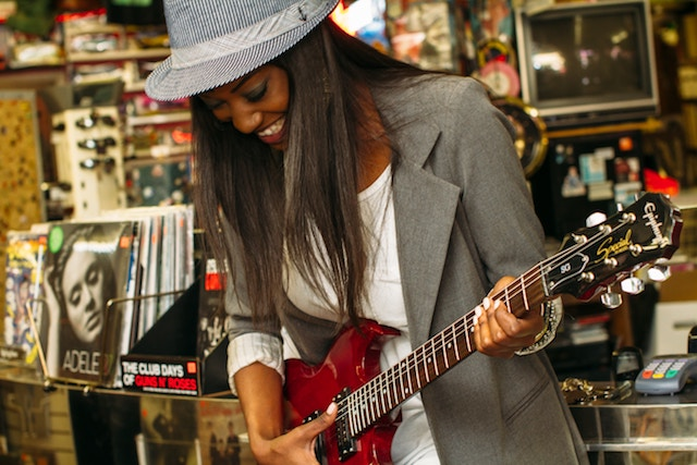 girl-playing-guitar-in-music-shop