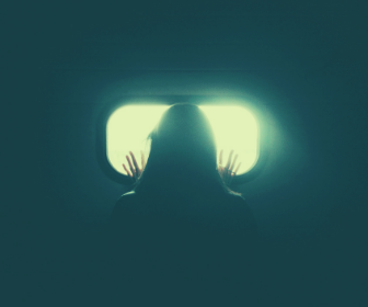 person-standing-in-front-of-oval-window-with-an-eerie-green-glow-hands-pressed-to-the-window