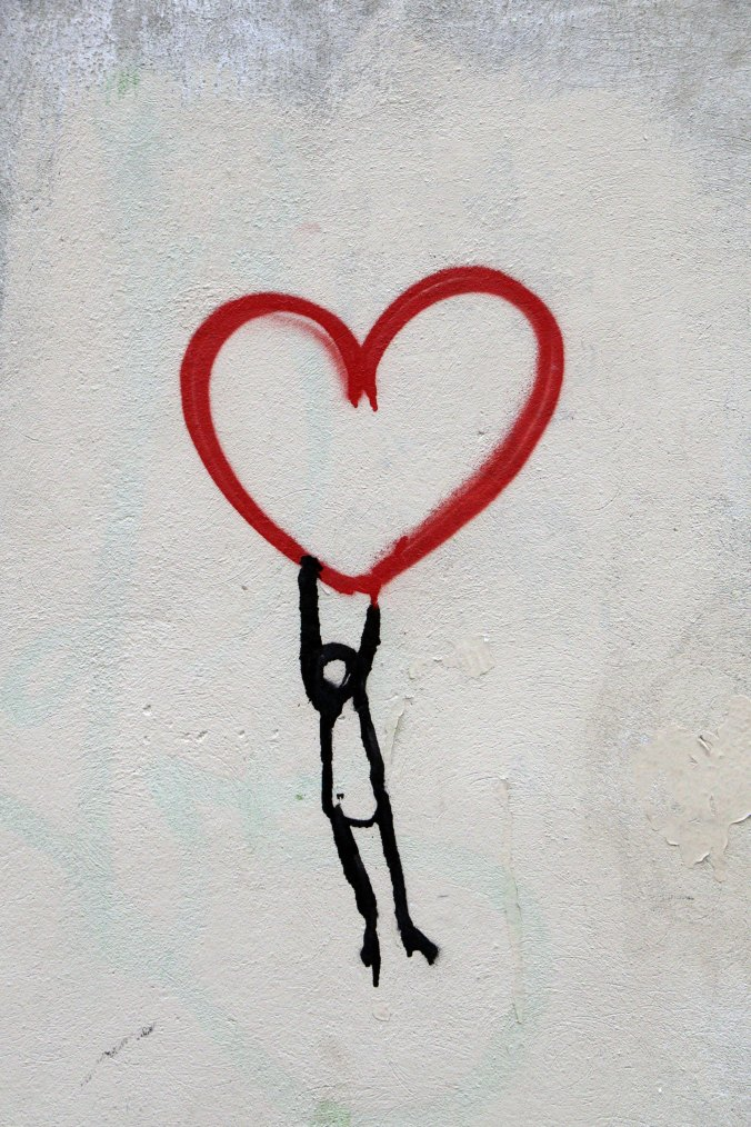 stick-figure-hanging-from-a-red-heart-shape-pointed-on-wall