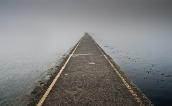 pathway through misty gray lake with two figures in the distance