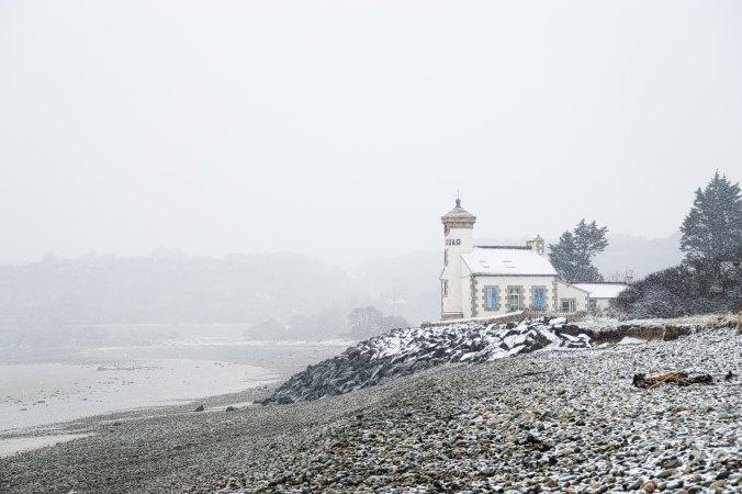lighthouse on a rocky seashore on a misty day