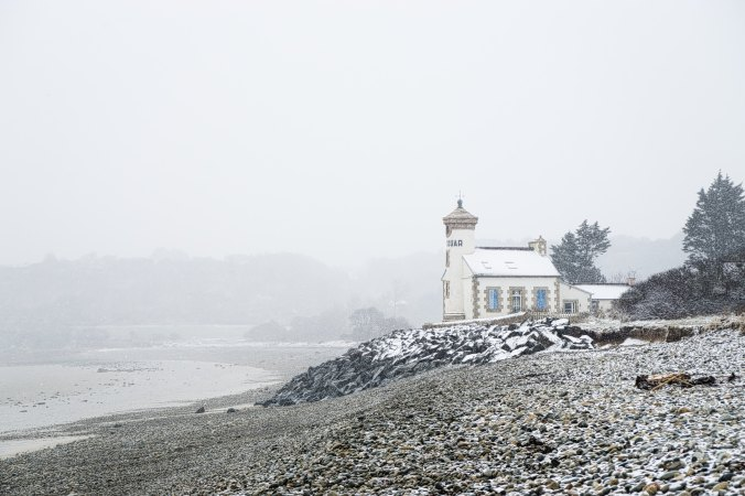 lighthouse on a rocky seashore on a misty day