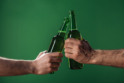 two male hands each holding a green beer bottle on a green background