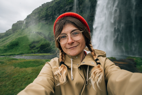 Happy smiling girl or young millennial hipster woman in red beanie, with two braids, glasses and raincoat makes selfie photo on smartphone in iceland, under epic waterfall, social media travel blogger
