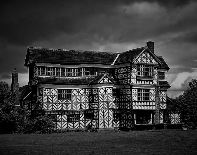 the image shows an ornately half-timbered house, bowed by the weight of centuries.