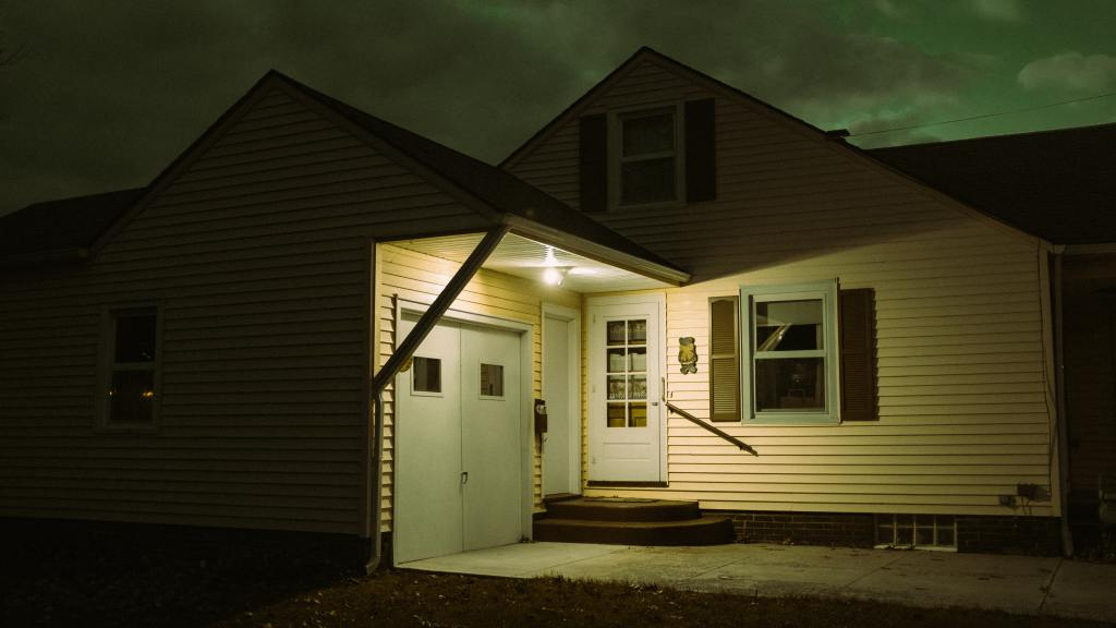 Yellow house at night with the porch light on.